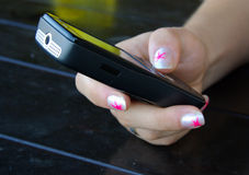 Girl holding a cell phone. A girl's hand holding a cell phone Stock Image