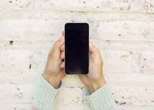 Girl holding cell phone and on a brick wall background. Close up Stock Images
