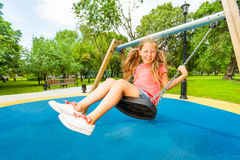 Girl holding chains of swings and swinging Stock Photo