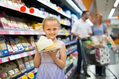 Girl holding cheese in hands in supermarket Royalty Free Stock Images
