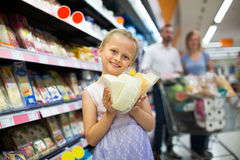 Girl holding cheese in hands in supermarket Stock Photos