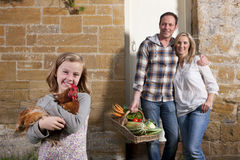 Girl holding a chicken, parents holding basket of vegetables Royalty Free Stock Photo