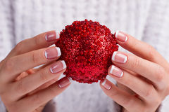 Girl Holding Christmas Ball In Fingers. Royalty Free Stock Photo