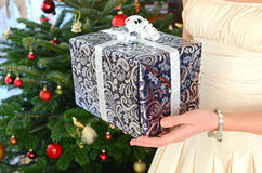Girl holding a Christmas gift. In the hands Royalty Free Stock Image