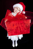 Girl holding christmas present. Smiling girl holding christmas present over dark Royalty Free Stock Images