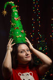 Girl holding a Christmas tree on background of twinkling lights. Girl holding a Christmas tree on a background of twinkling lights Royalty Free Stock Photography