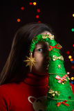Girl holding a Christmas tree on background of twinkling lights. Girl holding a Christmas tree on a background of twinkling lights Stock Photography