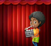 Girl holding clapboard in front of red curtain Stock Photography