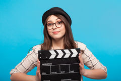 Girl holding clapperboard. Smiling young woman holding a clapperboard and looking at camera on the blue background Stock Photos