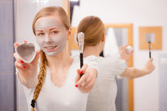 Girl holding clay mud mask and brush. Skin care. Stock Photography