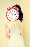 Girl holding clock in front of face. filtered image Stock Image