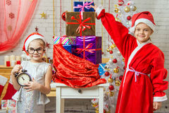 A girl holding a clock, a girl dressed as Santa Claus is standing at the bag with gifts Royalty Free Stock Image