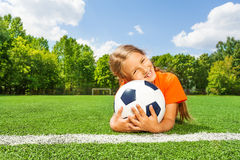 Girl holding close football, smiling and laying Royalty Free Stock Photo