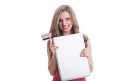 Girl holding closed laptop and a credit card Royalty Free Stock Images