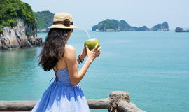 Girl holding coconut by the seaside Royalty Free Stock Images