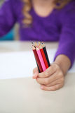 Girl Holding Of Colored Pencils In Classroom Royalty Free Stock Photos