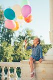 Girl holding colorful balloons looking to them while sitting in Royalty Free Stock Images