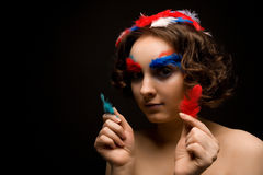 Girl holding colorful feathers Royalty Free Stock Photos