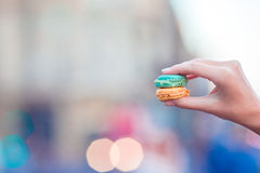 Girl holding colorful French macarons in hands background lively street. Girl holding colorful French macarons in hands stock image