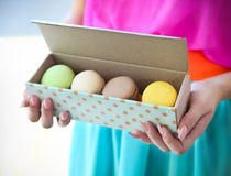 Girl holding colorful French macaroons in hands Stock Photos