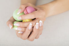 Girl holding colorful macaroons in hands with gel french manicure. Girl holding colorful macarons in hands with french manicure Royalty Free Stock Photography
