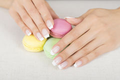 Girl holding colorful macaroons in hands with gel french manicure. Girl holding colorful macarons in hands with french manicure Stock Photo