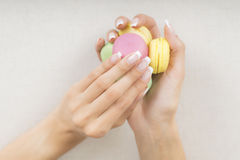 Girl holding colorful macaroons in hands with gel french manicure. Girl holding colorful macarons in hands with french manicure Royalty Free Stock Image