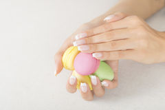 Girl holding colorful macaroons in hands with gel french manicure. Girl holding colorful macarons in hands with french manicure Royalty Free Stock Images