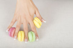 Girl holding colorful macaroons in hands with gel french manicure. Girl holding colorful macarons in hands with french manicure Royalty Free Stock Photo