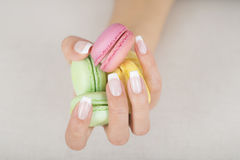 Girl holding colorful macaroons in hands with gel french manicure Royalty Free Stock Photography