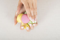 Girl holding colorful macaroons in hands with gel french manicure. Girl holding colorful macarons in hands with french manicure Stock Image