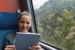 Young woman smiling and using a tablet for studying while travelling by train royalty free stock photography