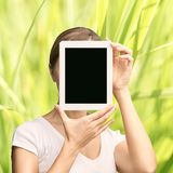 Girl holding computer pad. Mock up at tablet black screen. Face near laptop. Woman showing pc royalty free stock photo