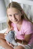 Girl holding conch shell. Caucasian pre-teen girl sitting indian style in rocking chair holding conch shell looking at viewer and smiling stock images