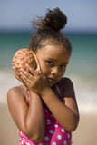 Girl holding conch shell next to her ear. royalty free stock photography