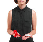 A girl holding a condom and a red ribbon isolated on a white background. Medical support. Safe sex propaganda concept. A red ribbon and a packed condom in hands Stock Images