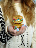 A girl holding cookies. A girl wearing knitted sweater is holding sandwich cakes royalty free stock photo