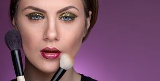 Girl holding cosmetic brushes to her face royalty free stock photos