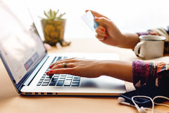 Girl holding credit card and typing on laptop, shop online home Royalty Free Stock Images