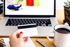 Girl holding credit card and typing on laptop, shop online home Stock Images