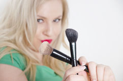 Girl holding crossed makeup brushes Stock Images