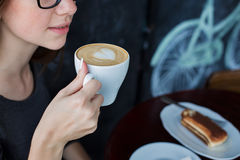 Girl holding a cup of coffee. In a cafe Royalty Free Stock Photos