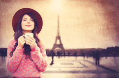 Girl holding cup of coffee on Eiffel tower background Stock Image