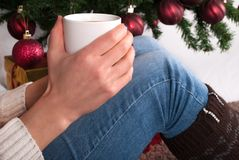 Girl holding cup of coffee in hand at legs with warmers and Christmas tree in the background. Young female legs with warmers on floor carpet holding cup coffee Royalty Free Stock Photos