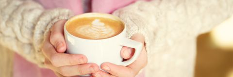 Girl holding a cup of coffee or hot chocolate or chai tea latte. Quiet hygge time concept. Warm tone. Horizontal, banner format Royalty Free Stock Photography