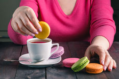 Girl holding a cup of coffee with macaroon Royalty Free Stock Photography