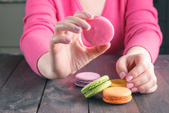 Girl holding a cup of coffee with macaroon Stock Photography