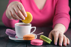 Girl holding a cup of coffee with macaroon Stock Photo