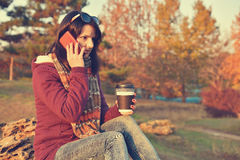 Girl holding cup of coffee and phone. Hipster girl holding cup of coffee and phone. Vintage photo stock images