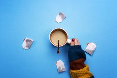 Girl holding a Cup of coffee surrounded by tea bags. The concept of beverages and preferences. Coffee pause, a break.  Stock Photo